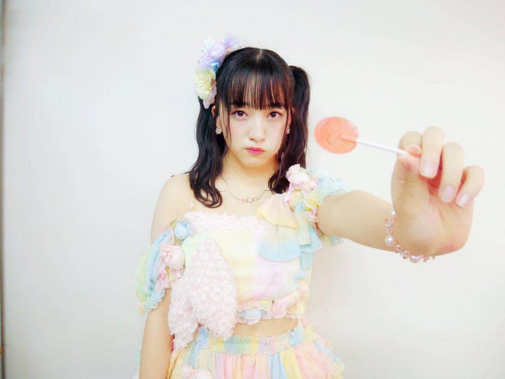 淡いパステルカラーの衣装でキャンディーを差し出すHKT48の田島芽瑠